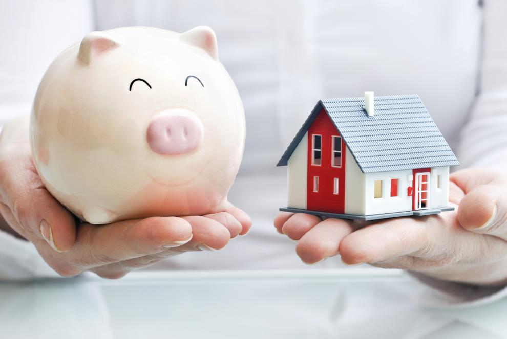 house and a piggy bank in hands