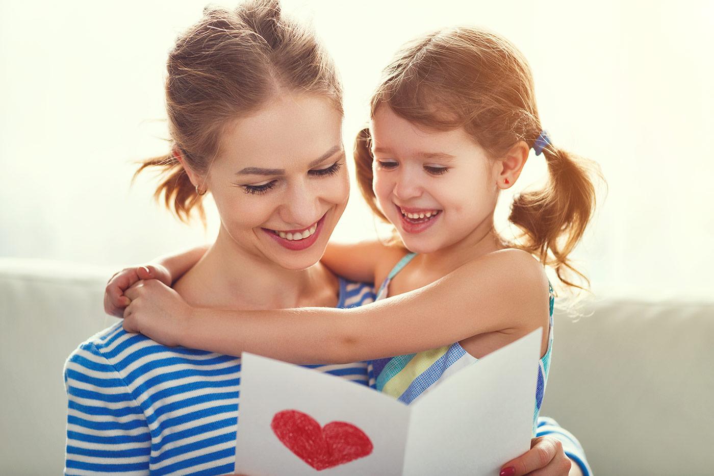 mère et sa fille tenant une carte de fête