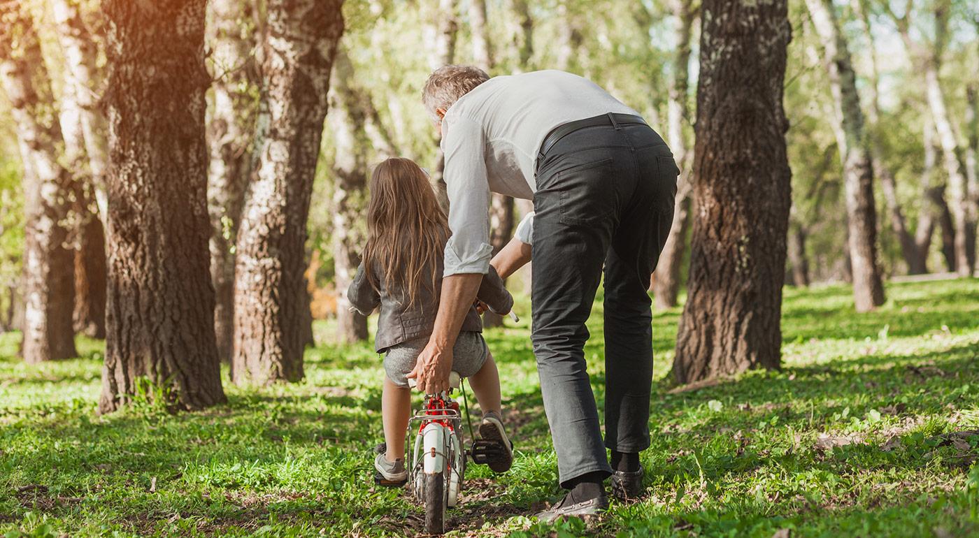 papa qui apprend à sa fille à faire du vélo