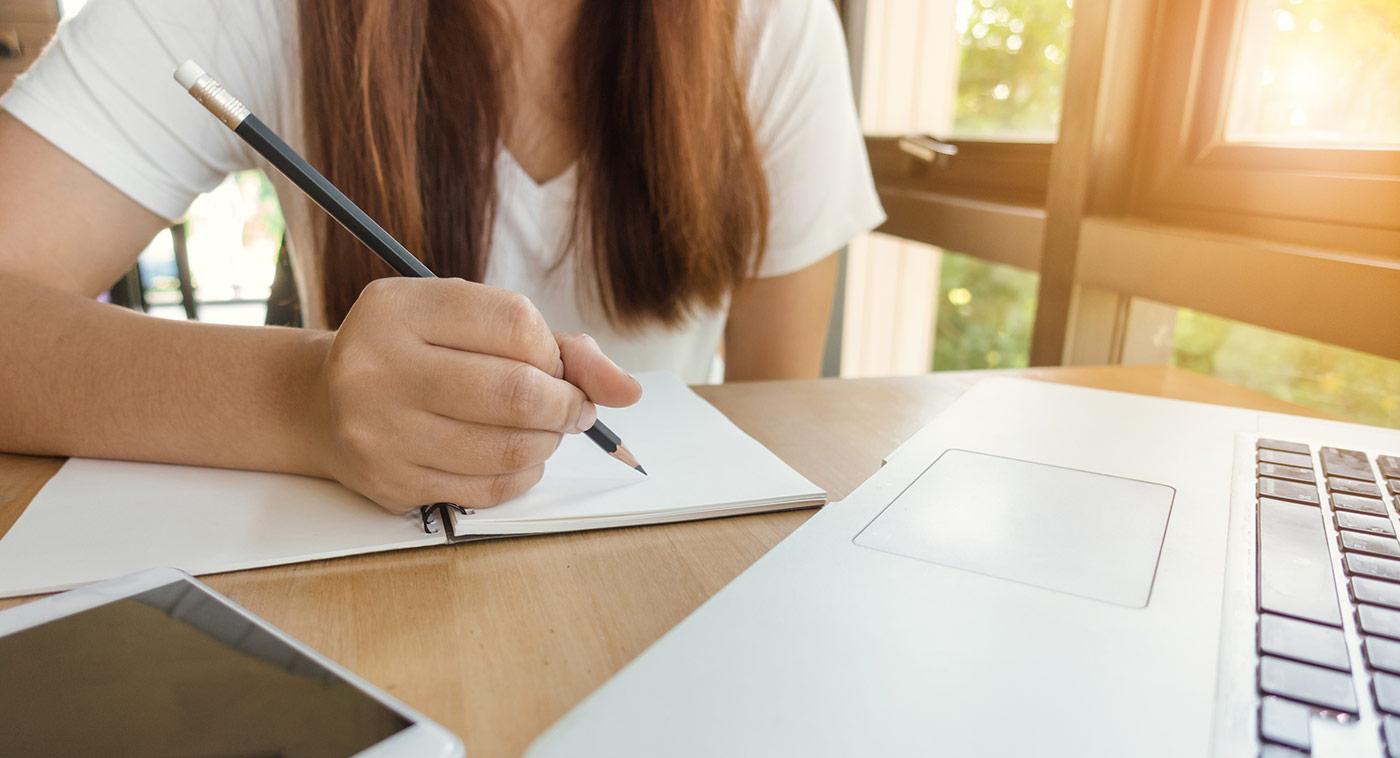 jeune femme écrivant dans un cahier de notes