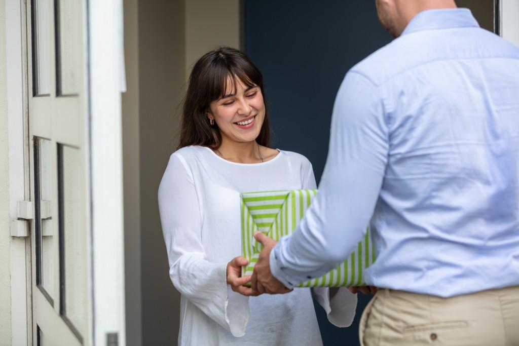 Homme offrant un cadeau à une femme dans une entrée.